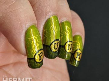 "A green gold circuit board mani with ""PUNK"" French tips and a cyberpunk mohawked lady on the thumb."
