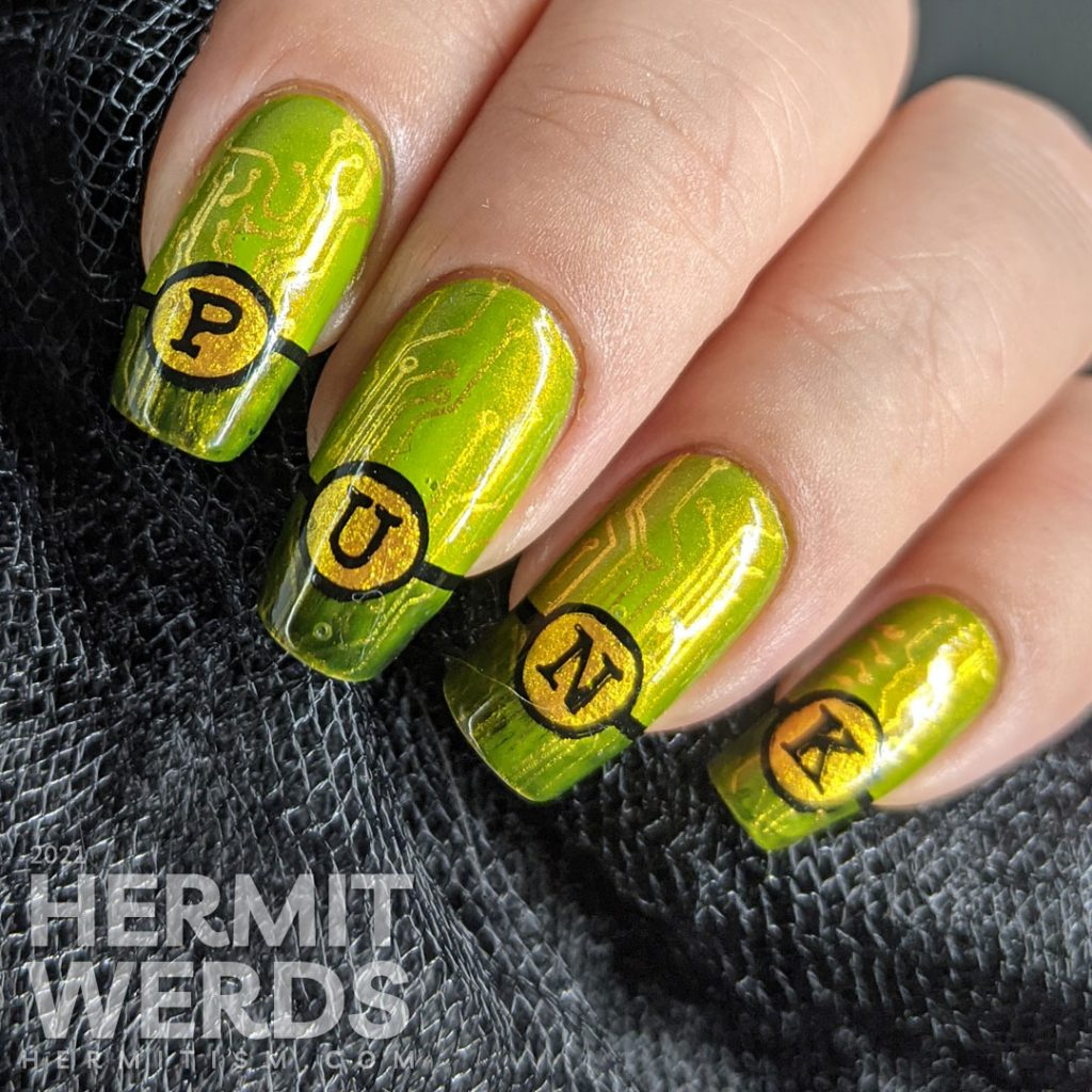 """A green gold circuit board mani with """"PUNK"""" French tips and a cyberpunk mohawked lady on the thumb."""