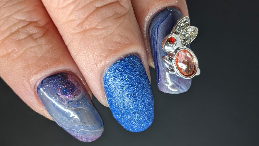 A blurple, blue, and grey with pink highlights fluid art nail design with a pink and silver bunny nail charm as accent.
