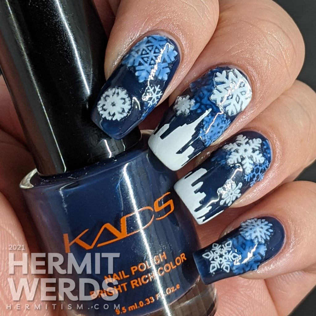 A pond mani with glow in the dark snowflake stickers and a white panoramic cityscape using a dark blue jelly polish.