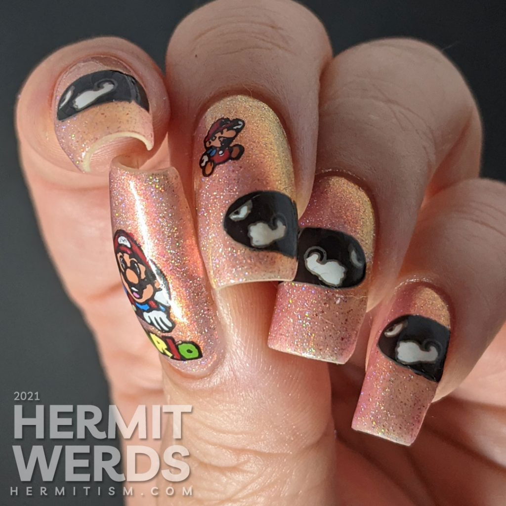 A pink to gold multichrome with holographic nail art featuring Nintendo's Mario dodging multiple Bullet Bills.