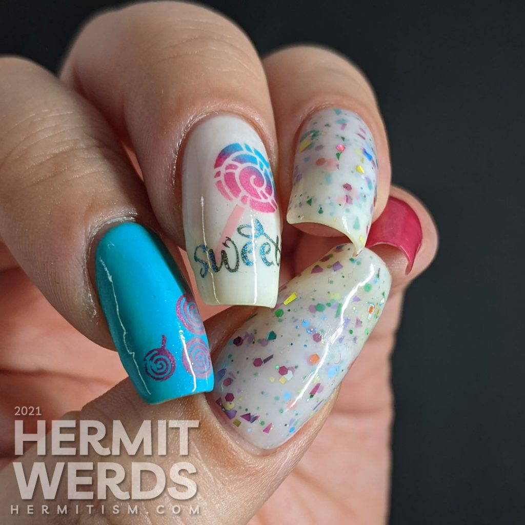 """Cute candy nail art in blue, pink, and white with lollipop stamping decals, the word """"sweet"""", and a rainbow crelly."""