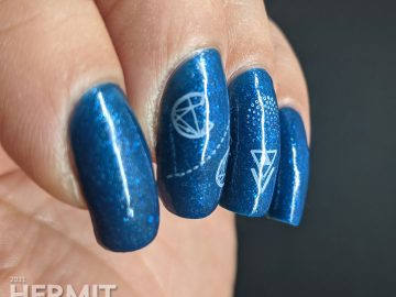 A medium blue polish with glitters and micro flakies with geometrically stylized cotton candy stamped on top.