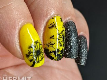A neon yellow crelly and black texture polish manicure with negative space black dandelions stamped on top. Glows in the dark.