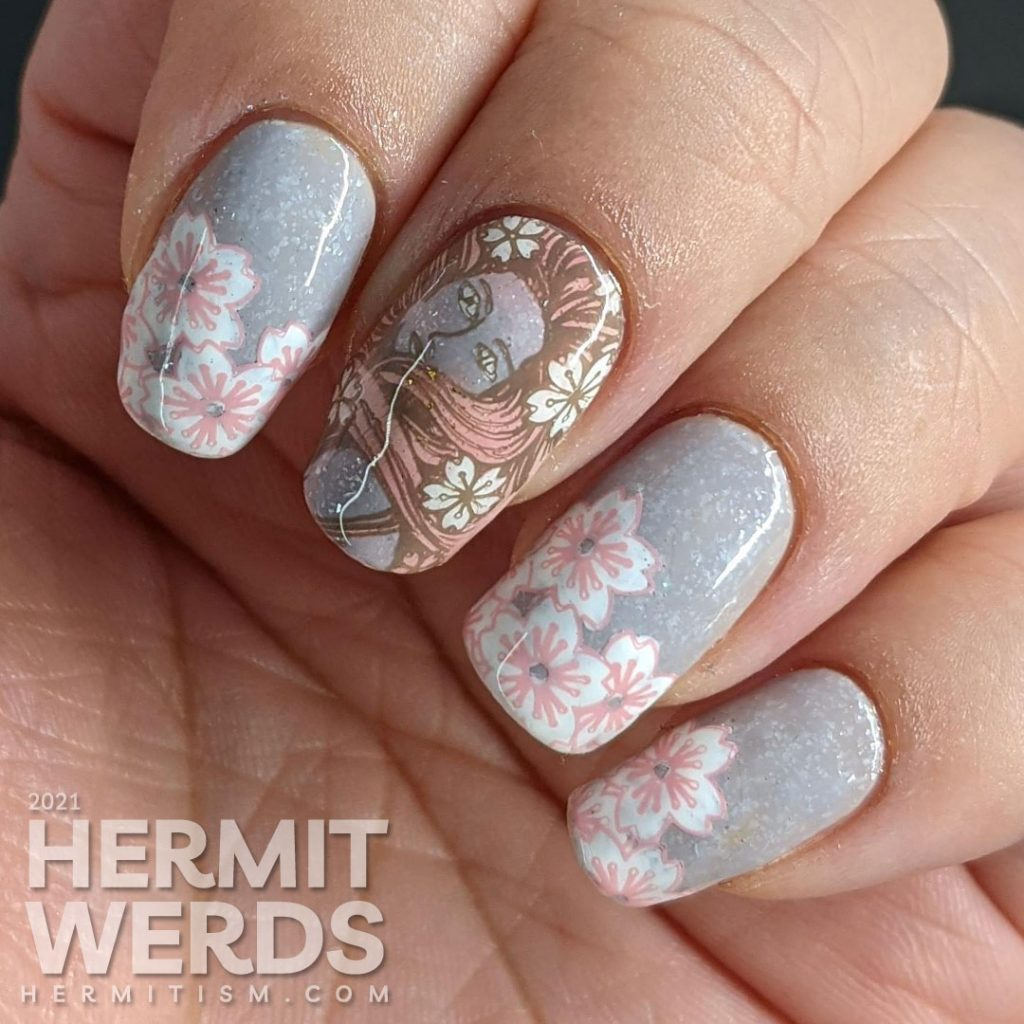 A soft grey nail art with stamping decals of sakura blossom French tips a pink-haired woman with more flowers and a blooming cherry tree.