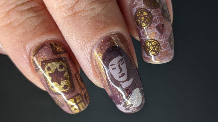 A mauve and gold magnetic nail art with tarot cards, the five of pentacles, all-seeing eye, and a fortune teller and her crystal ball.