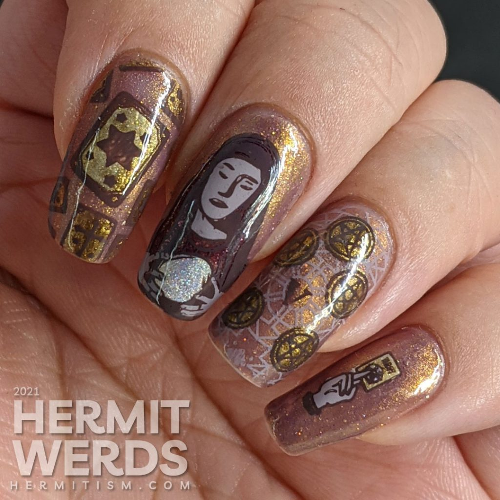 A mauve and gold magnetic nail art with tarot cards, the five of pentacles, all-seeing eye, and a fortune teller and her glass ball.