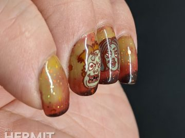 Zombie nail art with cartoon zombie head stamping decals and on a mustard/orange/brown tri-thermal base with orange and gold glitters.