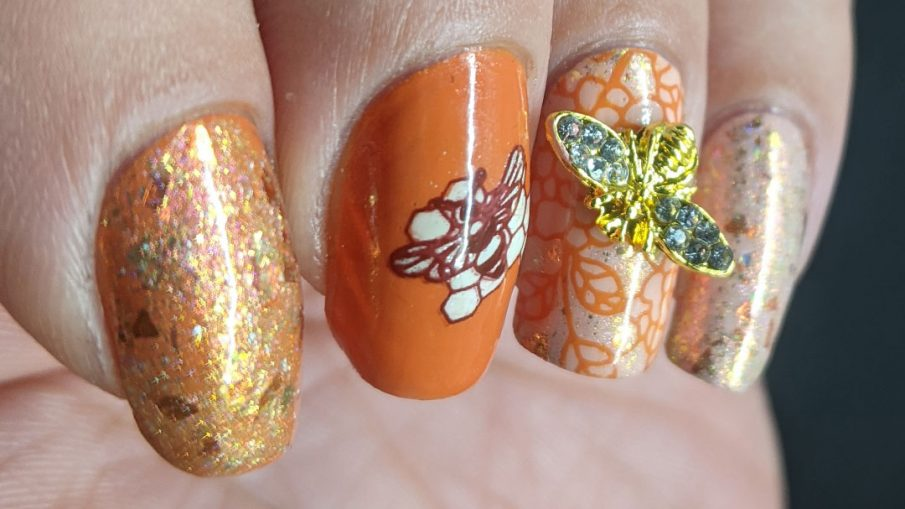 An orange and light pink mani with a super flakie rose gold topper, gold bee nail charm, and simple bee mosaic stamping decals.