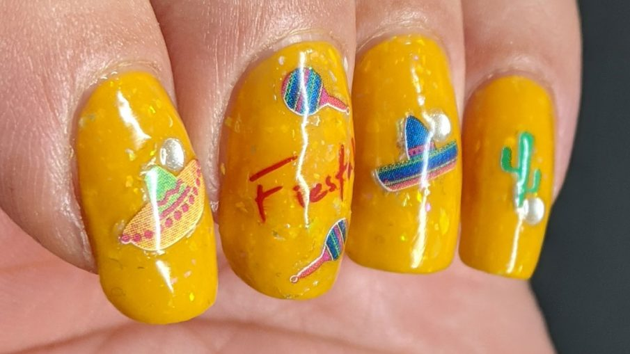 """Mexico-related nail stickers (hot peppers, sombreros, maracas, and a cactus) with the word """"fiesta"""" decorating a bright mustard crelly with iridescent flakes to celebrate Cinco de Mayo."""