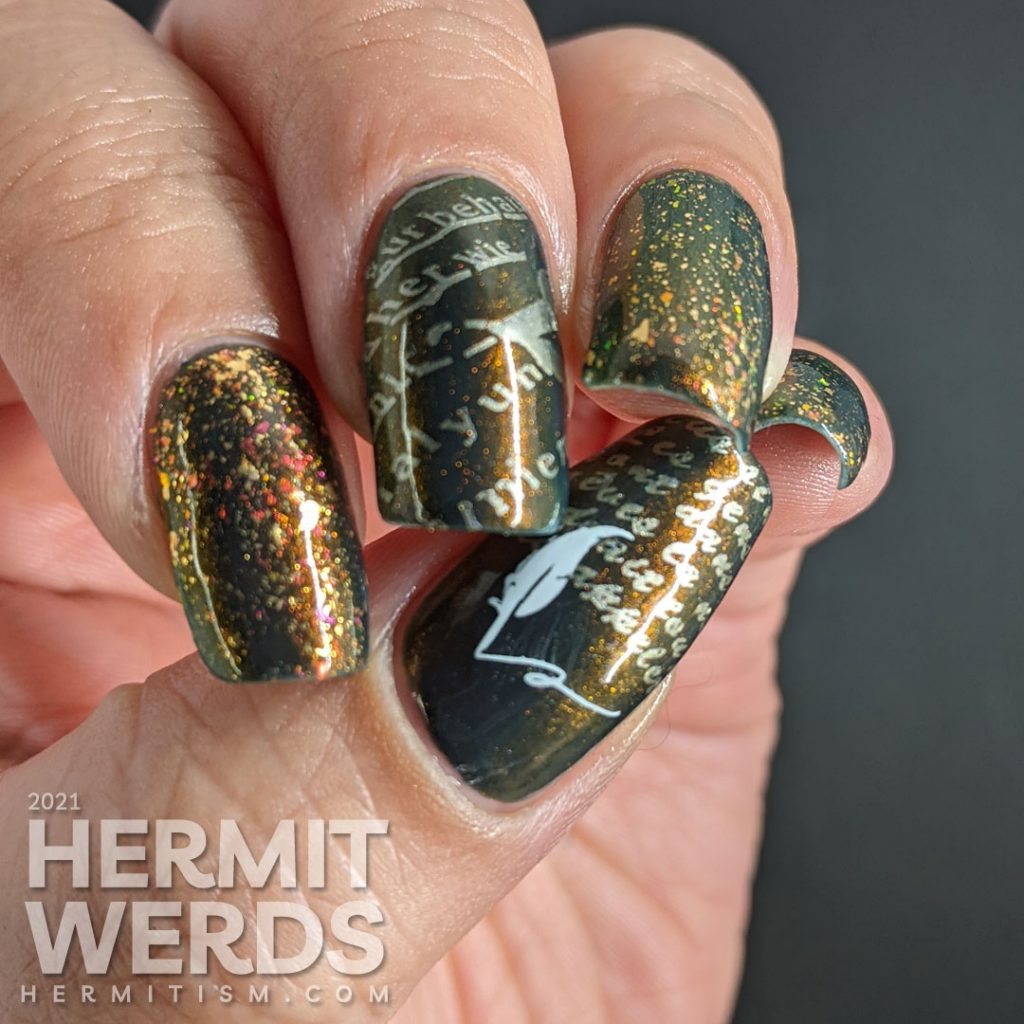 A smoky navy blue multichrome nail art with fake writing being highlighted (alphabet) stamping decals topped with a gold/iridescent topper.