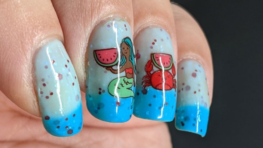 A turquoise to white thermal nail polish with stamping decals of a mermaid and crab enjoying watermelon and a full-nail watermelon pattern on the thumb.