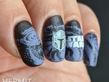 A black and purple Star Wars nail art with the Mandalorian's helm and Yoda silhouetted against a field of stars.