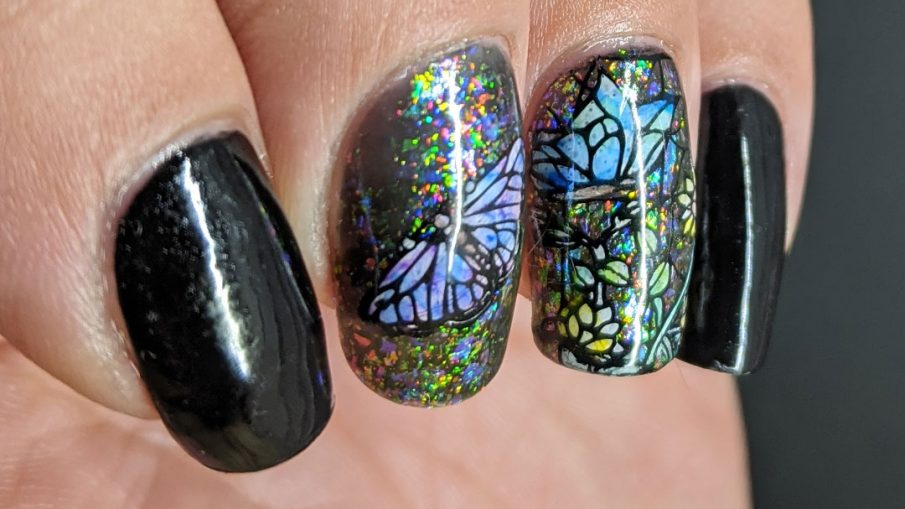 A stained glass butterfly nail art with an iridescent flakie topper and watercolor paint to fill in the butterfly decals.