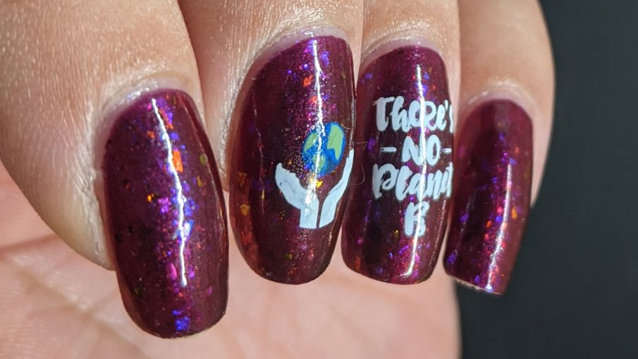 A plum flakie filled polish with earth-loving stamping images on top and a surprise nuclear explosion blowing up the planet. Oops!