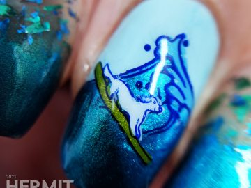 Shimmery blue and green ocean nail art with a stamping decal of a little white dog catching a wave/surfing.