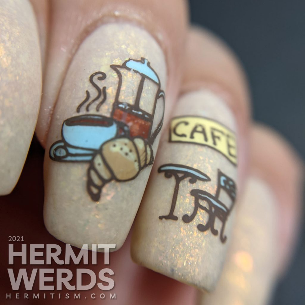 French nail art on a flakie-filled cream crelly with stamping decals of delicious French food like wine, croissants, and french press coffee.